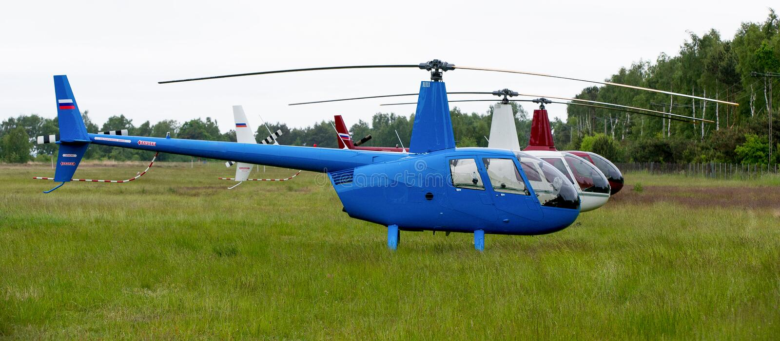 Three helicopters parked on a green field. During the International helicopter competition in Poland, three multicolored helicopters are parked in a green meadow royalty free stock photos