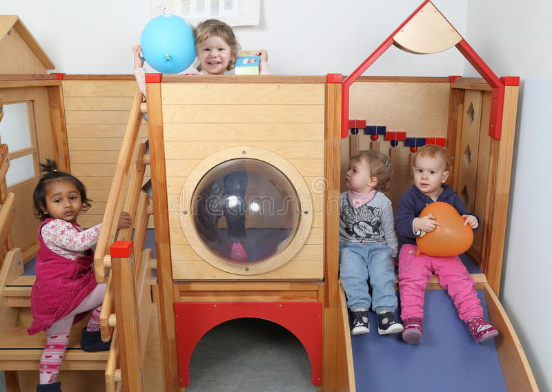 International Kindergarten with four kids playing on a slide royalty free stock images