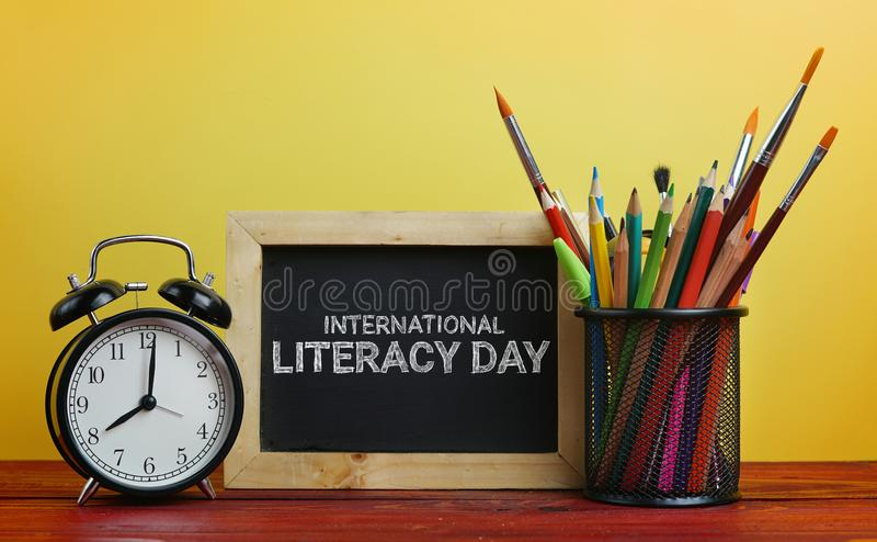 International Literacy Day. Alarm Clock, Blackboard and School S. Tationary in Basket on Wooden Table Yellow Background royalty free stock image