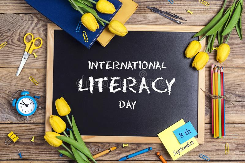 International Literacy Day background with a chalkboard, school supplies and tulip flowers. On a rustic wooden table royalty free stock photo
