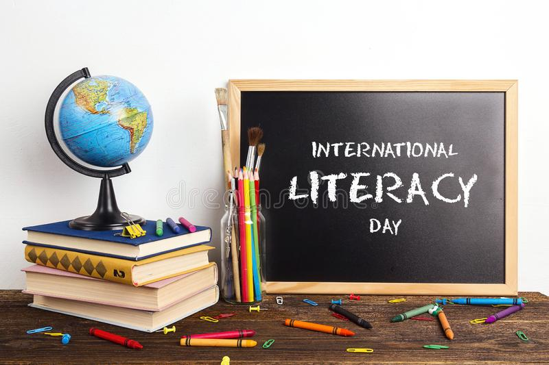 International Literacy Day. Chalkboard, a globe, a stack of books and school supplies. Banner for International Literacy Day with chalkboard, a globe, a stack of stock image