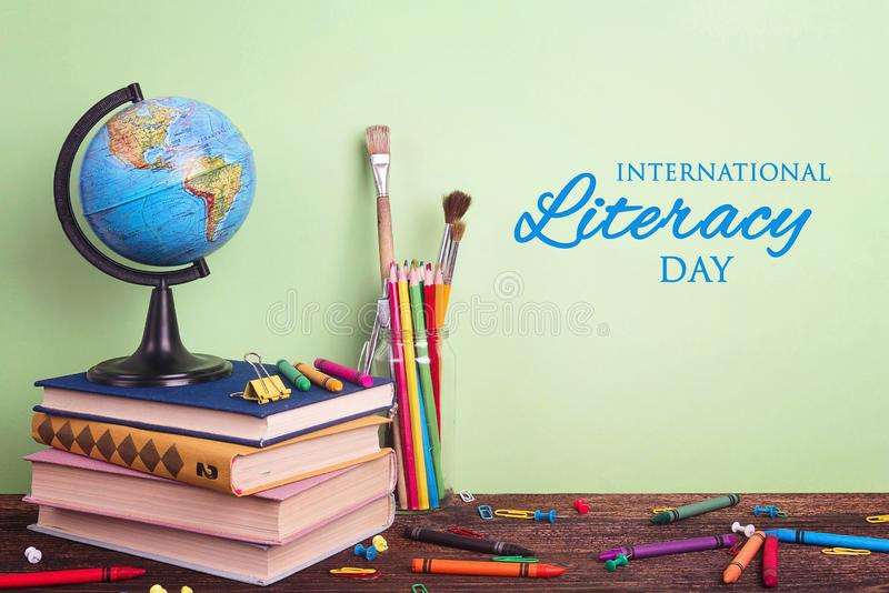 International Literacy Day composition with a globe, a stack of books and school supplies. On a green background stock photo