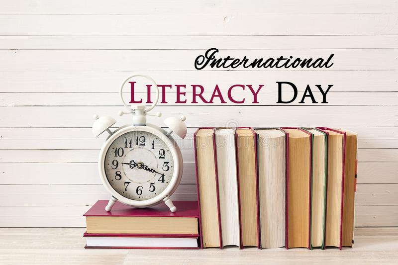 International Literacy Day concept with alarm clock and pile of books. On white wooden table stock photography