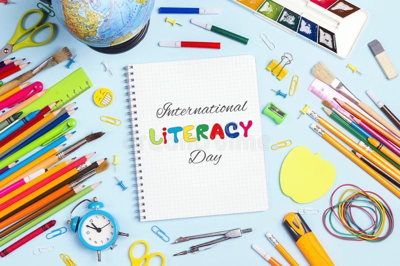 International Literacy Day concept with notebook and school supplies on blue background. Top down composition stock photos
