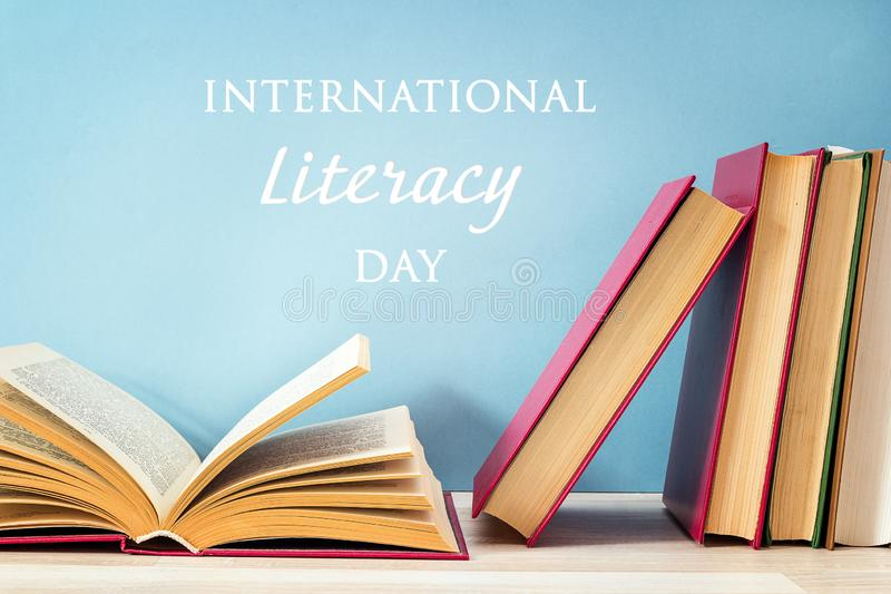International Literacy Day concept with stack of books on a blue background. International Literacy Day concept with stack of books with open book on a blue stock images