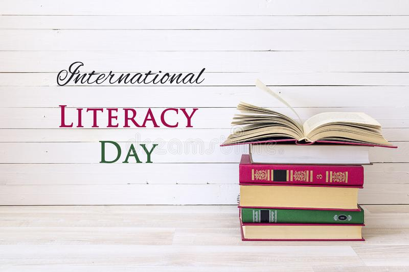 International Literacy Day concept with stack of books with open book. On white wooden table royalty free stock photo