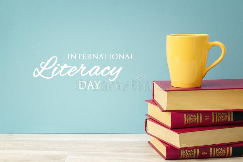 International Literacy Day concept with stack of books and yellow mug. Against blue background royalty free stock photos