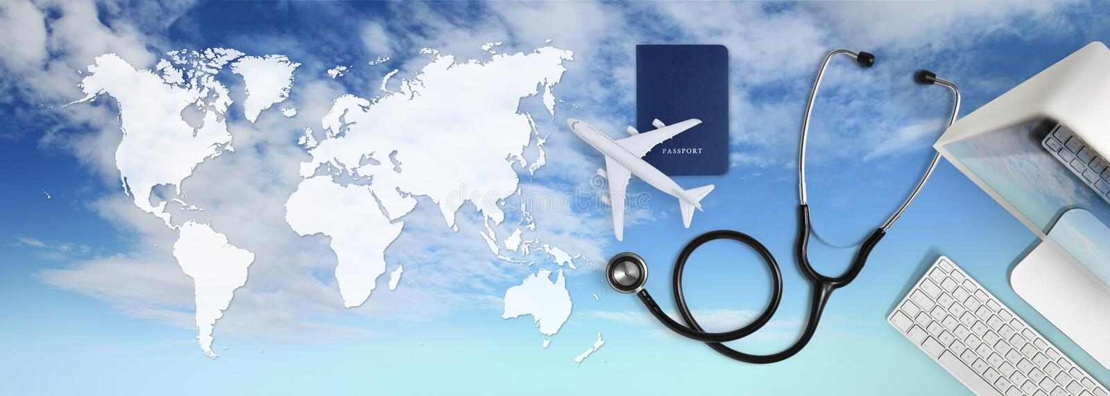 International medical travel insurance concept,stethoscope, passport, computer and airplane in sky background with global map. International medical travel royalty free stock photo