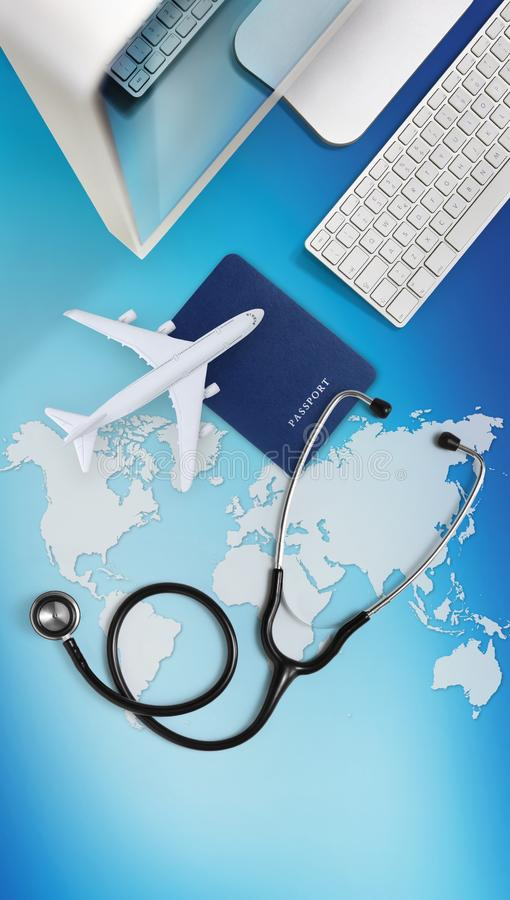 International medical travel insurance concept,stethoscope, passport, computer and airplane on sky background with global map. International medical travel stock photos
