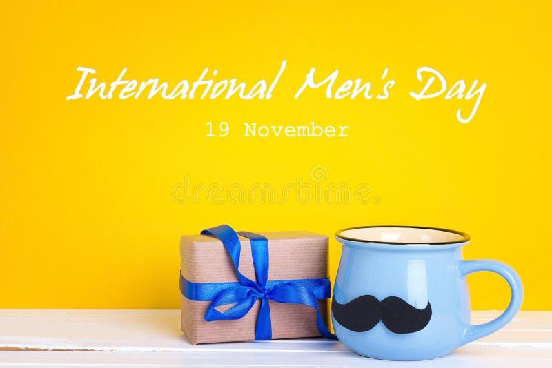 International men`s day background with mug with a mustache and. International men`s day background with blue mug with a mustache and gift box on yellow backdrop royalty free stock photos