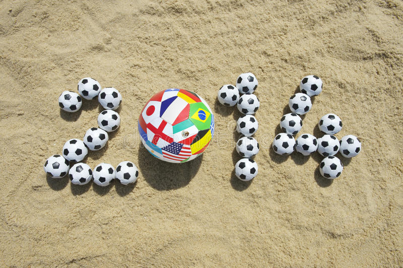 International 2014 Message in Sand with Football Soccer Balls. International 2014 football message made with country flag ball and small soccer balls on beach in royalty free stock images