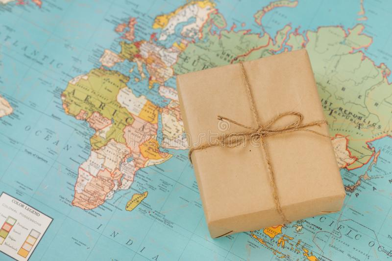 International shipping. Cardboard box on the geographical map ba. Ckground stock photos
