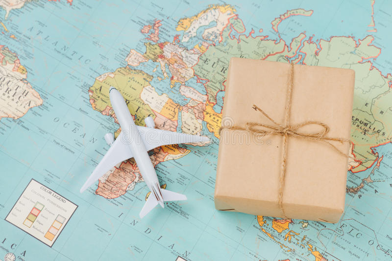 International shipping. White model airplane land on the geographical map background stock image
