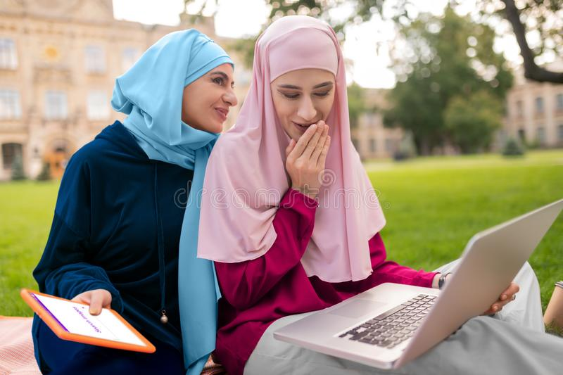 International students searching info in the Internet. Students searching info. International muslim students searching info in the Internet while sitting royalty free stock images