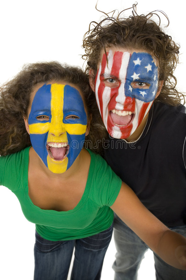 International supporters. Young screaming Swedish and American fans with painted flags on faces. They're looking at camera royalty free stock image