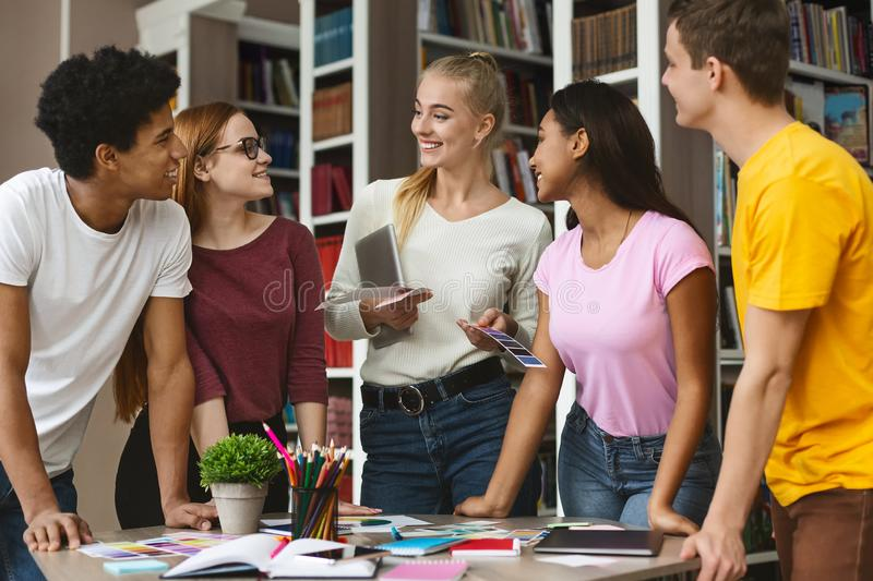International team of young designers discussing about project. International group of young designers discussing ideas for sketches, preparing for exam together royalty free stock images