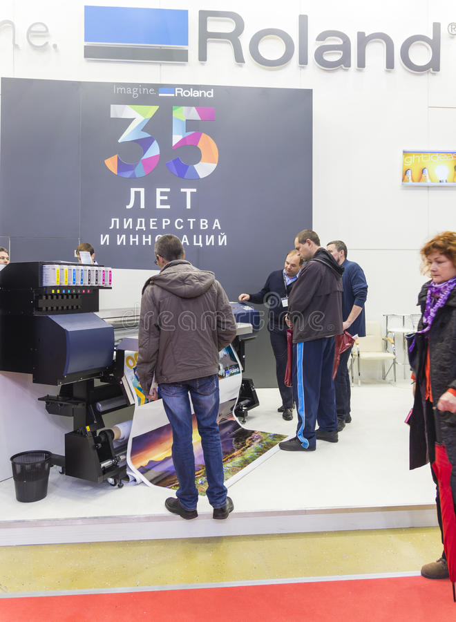 International Trade Fair REKLAMA. MOSCOW-SEPTEMBER 29, 2016: Business people are watching large format printer brand Roland at the International Trade Fair royalty free stock photography
