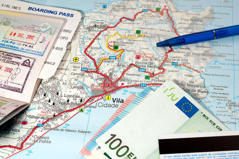 International travel concept. Passport, boarding pass, money, credit card, pen on map of tropic island. Angle view royalty free stock photo