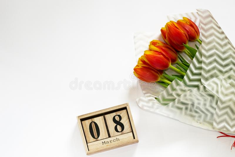 International Women`s day background with bouquet of red tulips and wooden calendar of 8 march. Copy space for text. Beauty blog. Composition top view royalty free stock photos