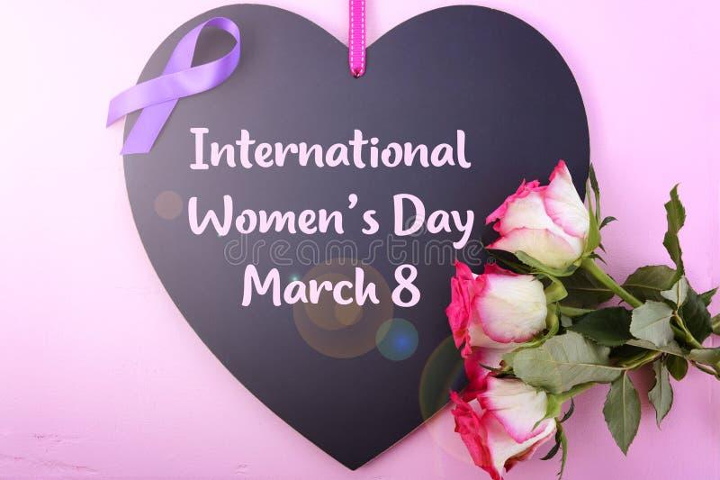 International Women`s Day Notice Board Greeting with lens flare. International Women`s Day, March 8, heart shaped blackboard greeting with purple ribbon symbol royalty free stock photography