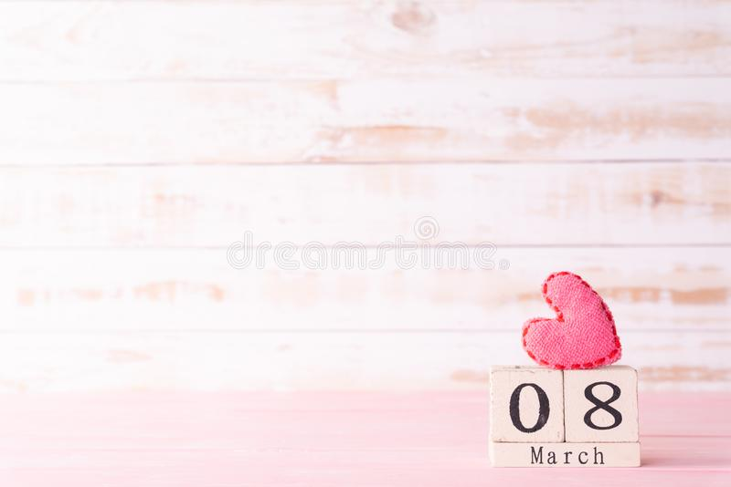 International Womens day concept. March 8 text on wooden block with handmade pink heart on white wooden background stock images