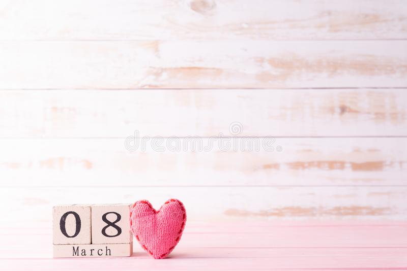 International Womens day concept. March 8 text on wooden block with handmade pink heart on white wooden background royalty free stock images
