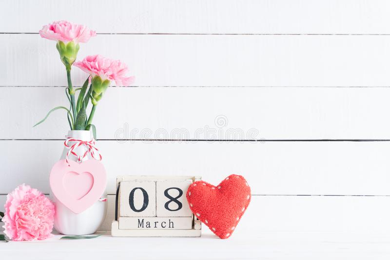 International Womens day concept. Pink carnation flower in vase and red heart with March 8 text on wooden block calendar on white royalty free stock photography