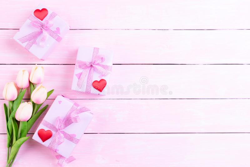 International Womens day concept. Pink tulips and red heart with gift box on white and pink wooden background stock photography