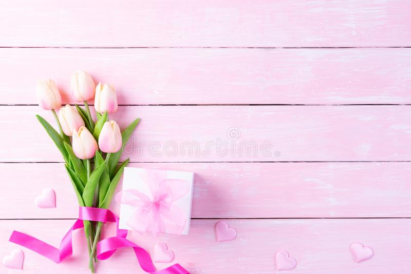 International Womens day concept. Pink tulips and red heart with gift box on white and pink wooden background royalty free stock image