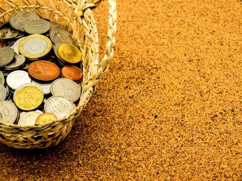 Internationale alte Münze im Korb auf Korkenbrett stockfotografie