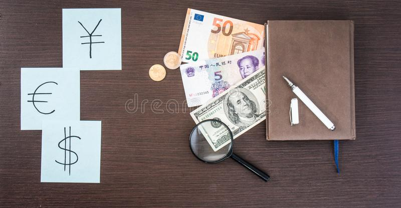 Internationale Bankbiljetten, muntstukken, blocnote, stickers met munttekens op houten lijst De ruimte van het exemplaar stock foto's
