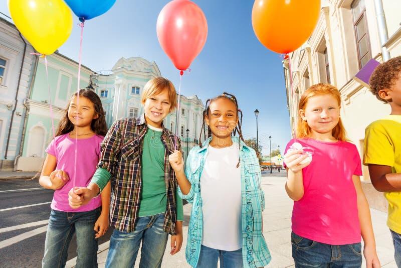 Internationale groep kinderen met ballons stock afbeeldingen