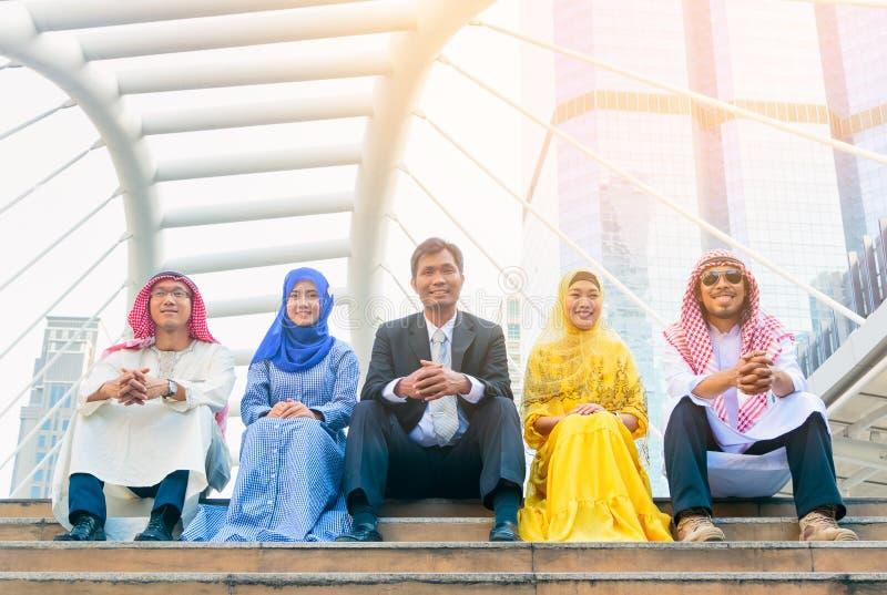 Internationale Gruppe Geschäftsmänner und Frauen, die in der Stadt sitzen lizenzfreie stockbilder