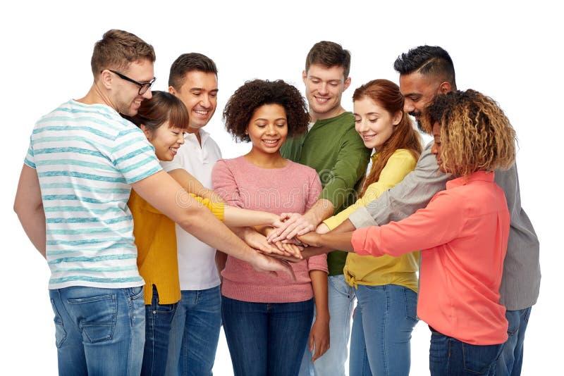 Internationale Gruppe Händchenhalten der glücklichen Menschen stockfotografie