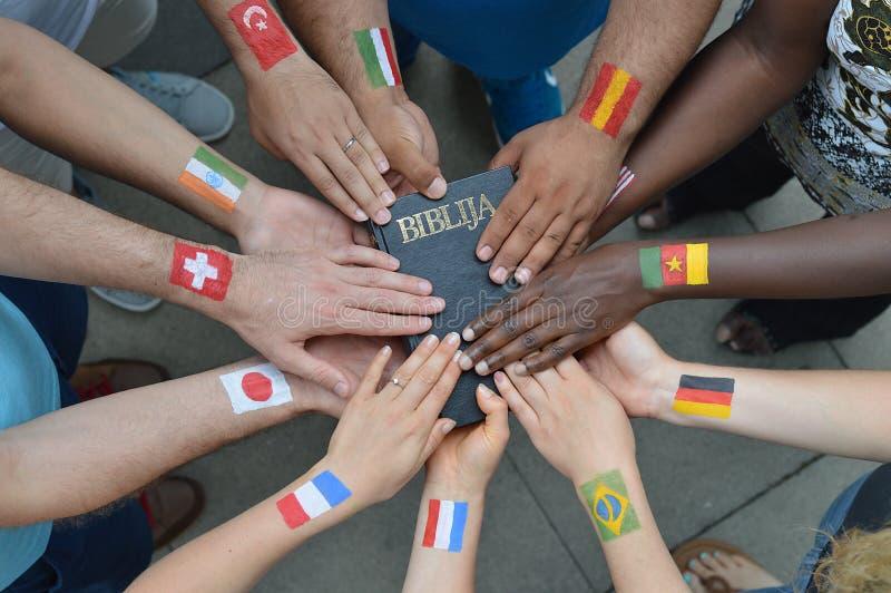 Internationale Leute mit den Flaggen, die eine Bibel halten stockbild