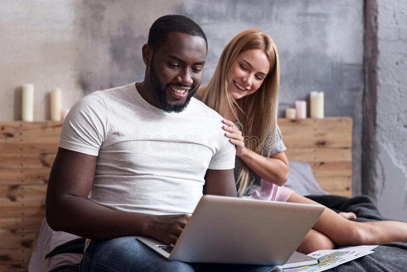 Internationale Paare, die glücklich im Schlafzimmer mit Laptop sitzen stockfotos