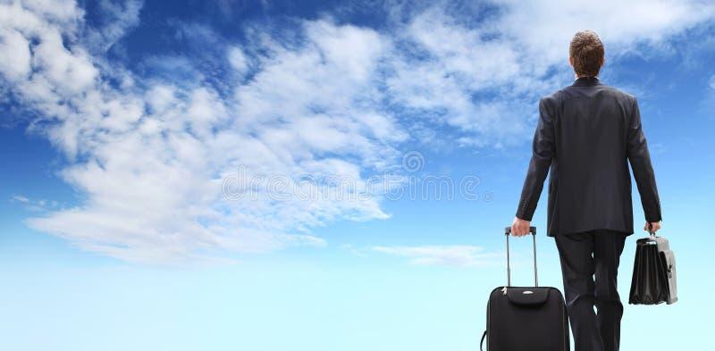 Internationale reis bedrijfsmens, succesconcept, zakenman achtermening met karretje lopen en aktentas die, die op bluhemel wordt  stock foto's