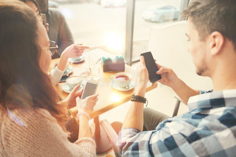 Internationale Studenten, die intelligentes Telefon im Café verwenden stockfotos