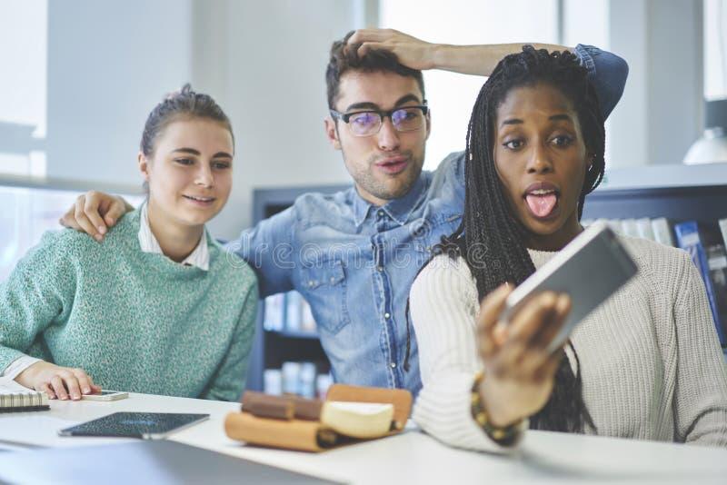 Internationale studenten die van vrije tijd genieten die grappige beelden op mobiel telefoonapparaat maken stock fotografie