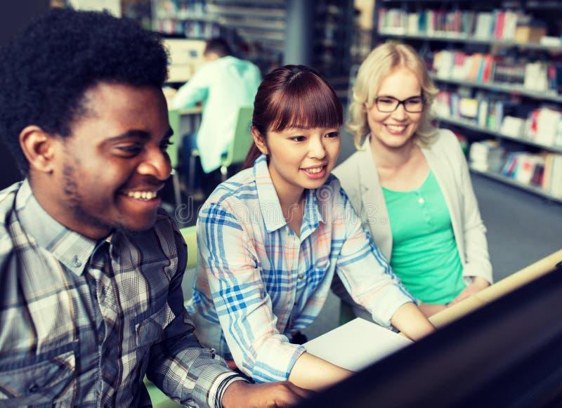 Internationale studenten met computers bij bibliotheek royalty-vrije stock foto's