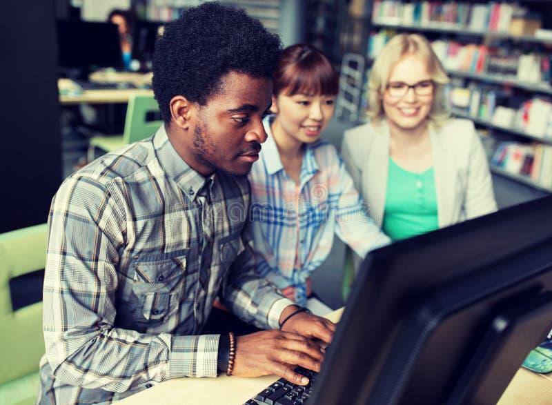 Internationale studenten met computers bij bibliotheek stock foto's
