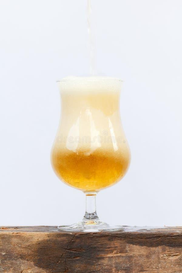 Internationaler Biertag mit strömendem Bier in Glas auf weißem BAC lizenzfreies stockbild