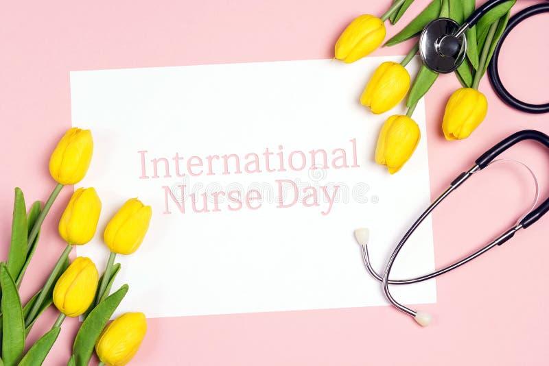 Internationaler Krankenschwester-Day-Hintergrund mit gelben Tulpen und Stethoskop auf Rosa lizenzfreie stockfotos
