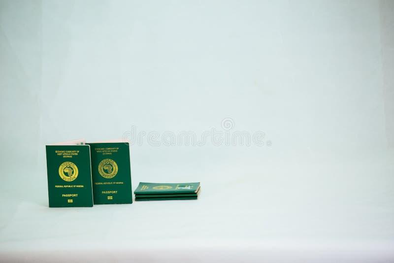Internationaler Pass Ecowas Nigeria auf Haufen des Nairabargeldes stockbilder