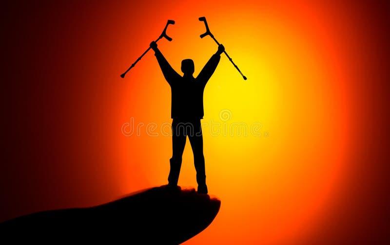 Internationaler Tag von Personen mit Konzept der Unfähigkeit (IDPD): Silhouettieren Sie einen behinderten Mann, der oben steht un stockbild