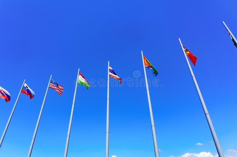Internationalflaggor mot blå himmel royaltyfri fotografi