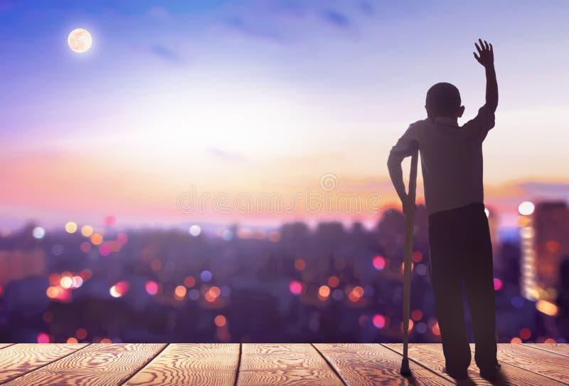 Internationell dag av personer med konturn för š för handikappconceptï¼ ett rörelsehindrat mananseende på bergstadsbakgrund arkivfoton