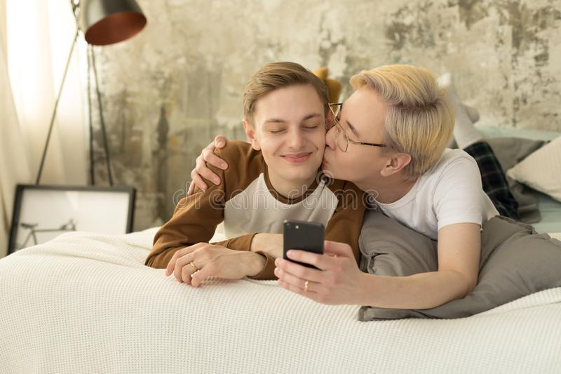 internationell f?r?lskelse Homosexuell asiatisk man med blont h?r som kysser hans europeiska pojkv?n och tar selfiefotoet royaltyfri fotografi
