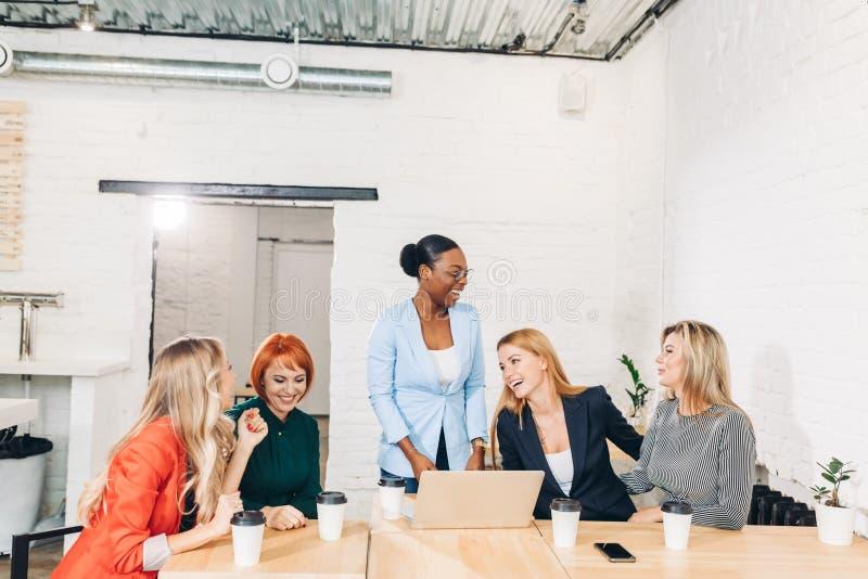 Internationell grupp av lyckliga kvinnor som firar framgång på lagmötet royaltyfri bild