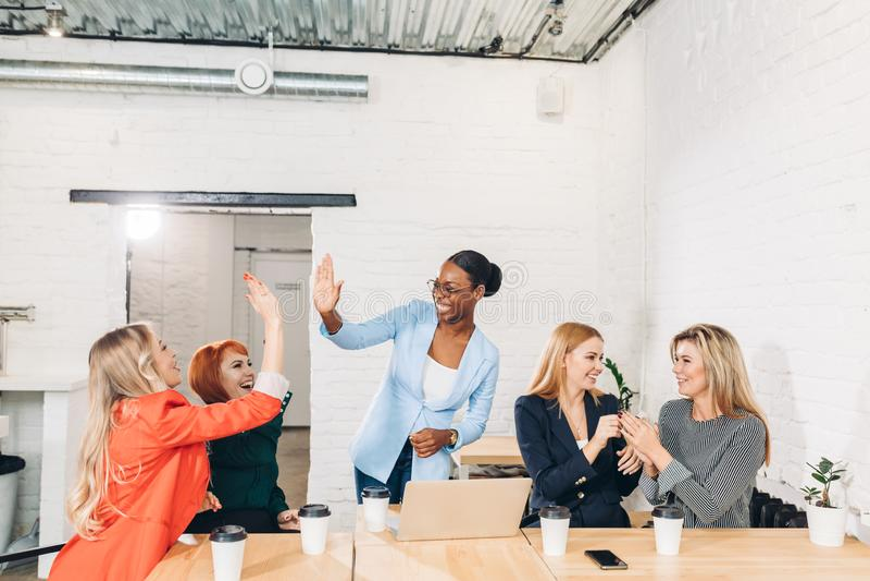 Internationell grupp av lyckliga kvinnor som firar framgång på lagmötet royaltyfria bilder